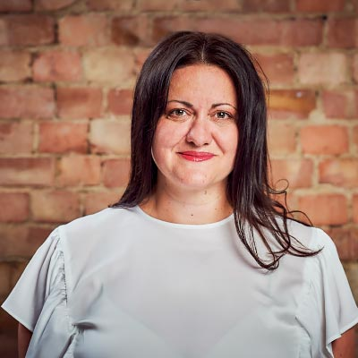 A colour head and shoulder photo of Maki Andonova Financial Controller at Westhill against a brick wall backdrop