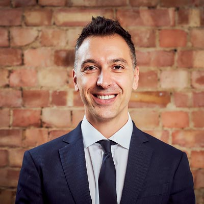 A colour head and shoulder photo of Roberto Napolitano Marketing Director at Westhill against a brick wall backdrop