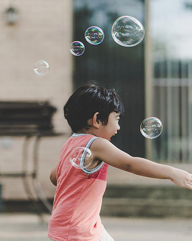 A colour image of a Chinese boy playing and blowing bubbles used in the work in our communities section of the corporate social responsibility page - Westhill Property Investments