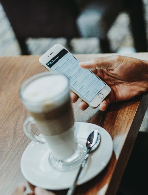 A colour image of a business man on his mobile phone with a latte coffee used on the Westhill Real Estate investors contact page