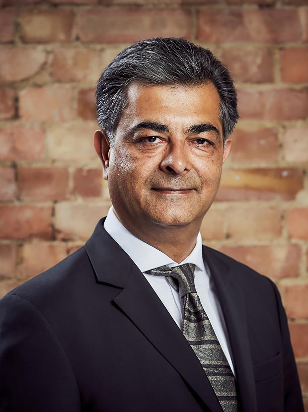 A colour head and shoulder photo of Minesh Sheta Chief Financial Officer at Westhill against a brick wall backdrop