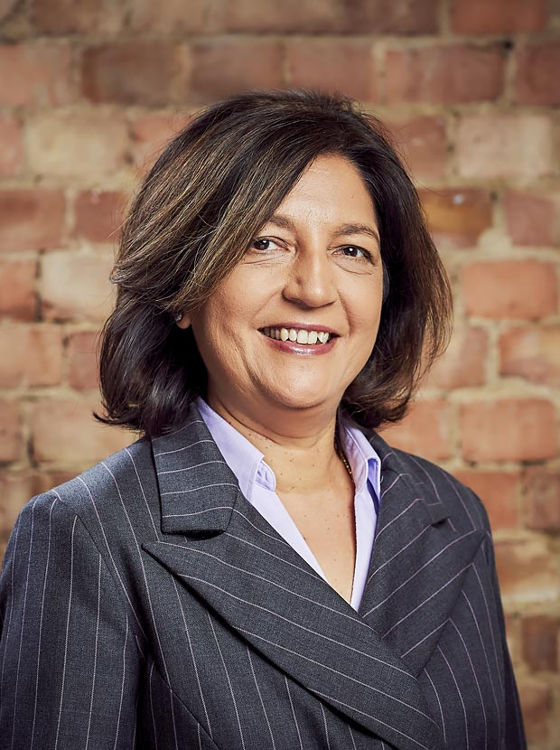A colour head and shoulder photo of Rita Dattani Chief Executive Officer at Westhill against a brick wall backdrop